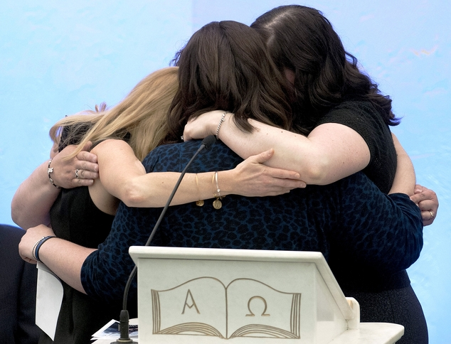 Family members embrace after eulogizing Auburn Police Officer Ronald Tarentino, Jr., of Leicester, Mass., during a funeral service at St. Joseph's Church in ...