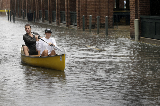 FILE- In this Oct. 3, 2015 file photo, Dillon Christ, front, and Kyle Barnell paddle their canoe down a flooded street in Charleston, S.C. The U.S. governmen...