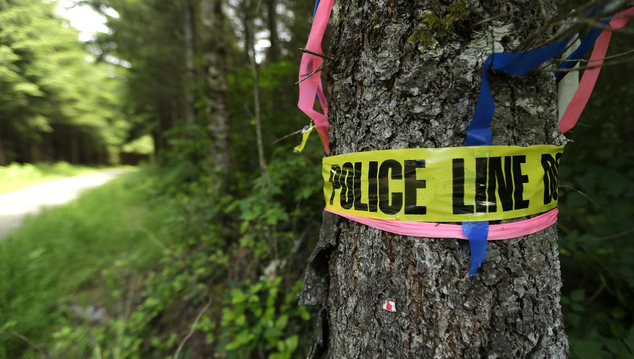 In this Wednesday, May 25, 2016 photo, police crime-scene tape rings a tree near where the remains of a local couple were found the day before near Oso, Wash...