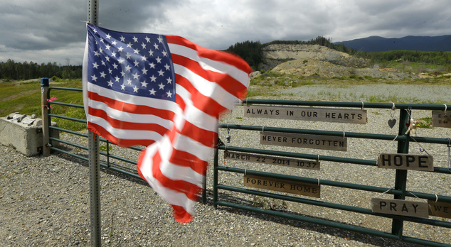 In this Wednesday, May 25, 2016 photo, a U.S. flag flutters in the wind near the site of a massive 2014 mudslide that killed 43 people in Oso, Wash. Patrick ...