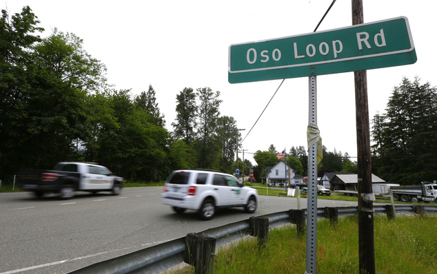 In this Wednesday, May 25, 2016 photo, cars pass Oso Loop Road near the site of a massive 2014 mudslide that killed 43 people in Oso, Wash. Patrick Shunn and...