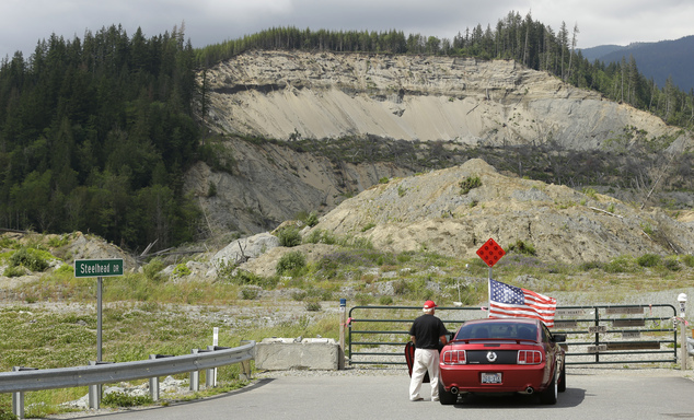 In this Wednesday, May 25, 2016 photo, a motorist pauses near a U.S. flag that had been placed near the site of a massive 2014 mudslide that killed 43 people...