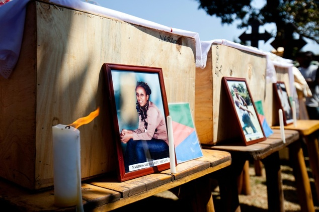 Pictures of some of the victims are laid before their caskets at a memorial service in July 2010 for six young Eritreans killed in the Kampala bombing