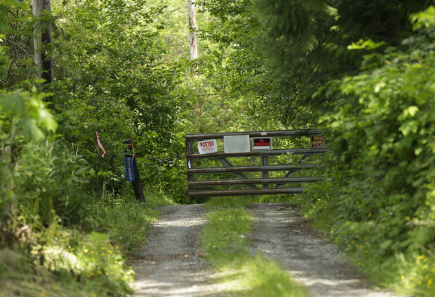 In this Wednesday, May 25, 2016 photo, a locked gate blocks a road leading to a house belonging to Patrick Shunn and Monique Patenaude, in Oso, Wash. Authori...