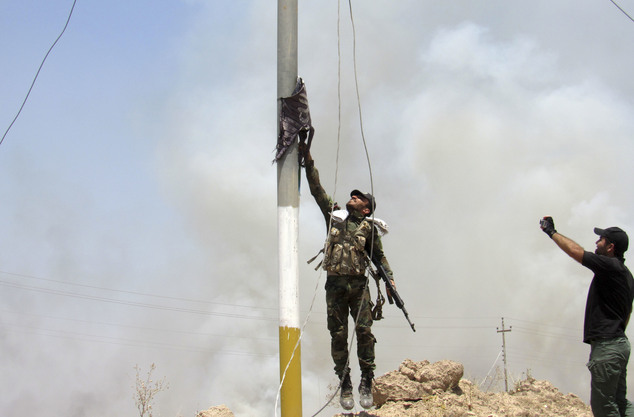 FILE - A fighter with Badr Brigades Shiite Popular Mobilization Forces takes down a flag of the Islamic State group outside Fallujah, 40 miles (65 kilometers...