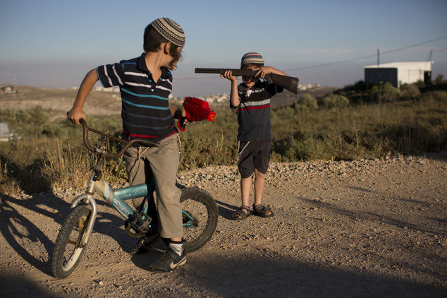 FILE - In this Wednesday, May 18, 2016 photo, Jewish settler boys play with toy guns in Amona, an unauthorized Israeli outpost in the West Bank, east of the ...