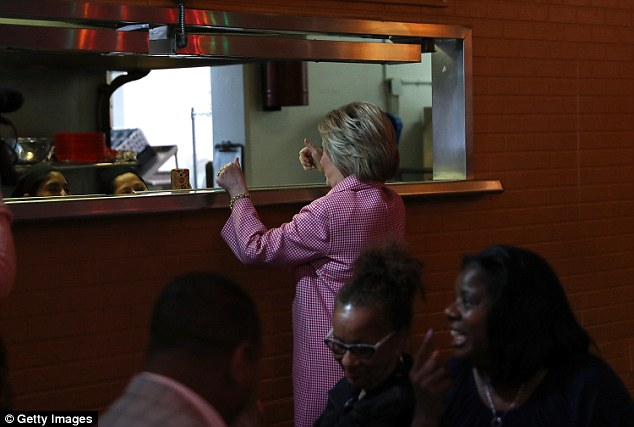 Clinton's outfit on Friday seemed strangely shapeless as she stood up to gesture at the diner's kitchen staff (pictured). Pink gingham became increasingly popular in the 1950s