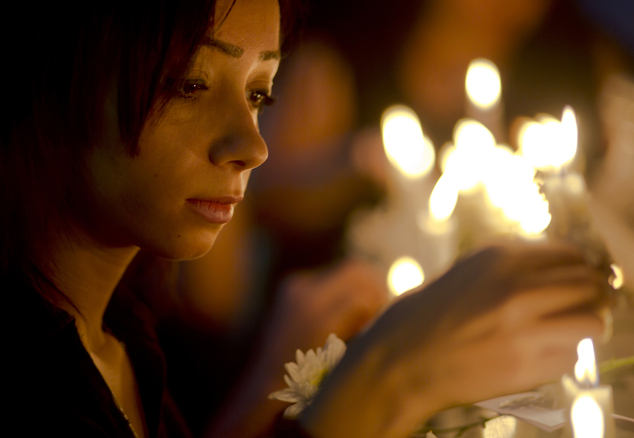FILE - An Egyptian journalist lights candles during a candlelight vigil for the victims of EgyptAir flight 804 in front of the Journalists' Syndicate in Cair...