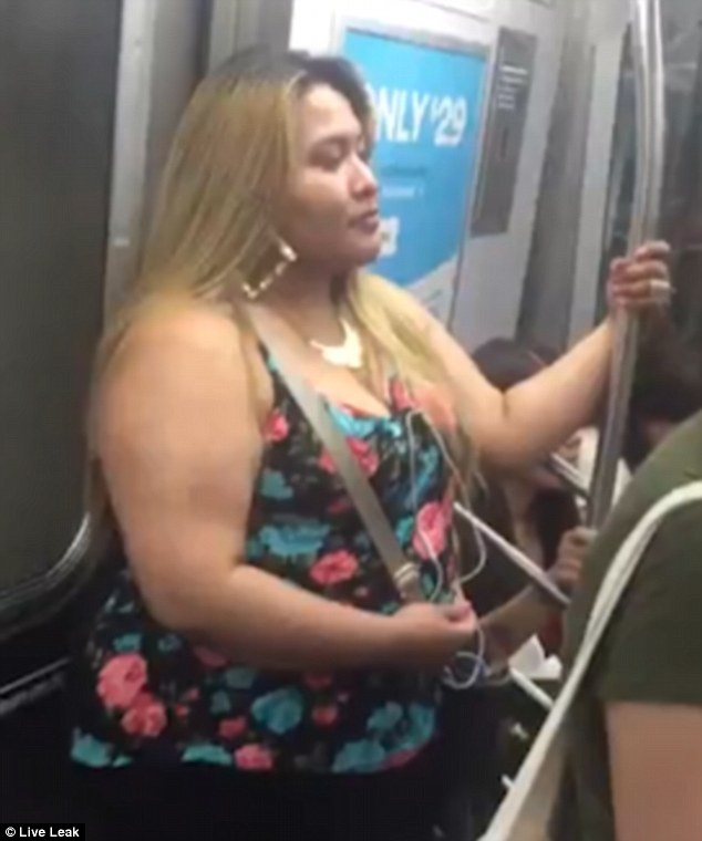 Shameless? The woman riding the New York subway stands untroubled after allegedly taking his cash