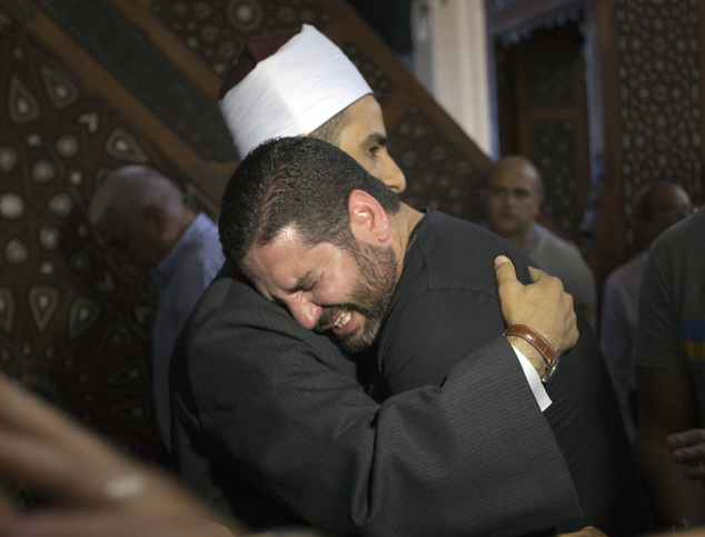 FILE - In this Friday, May 20, 2016 file photo, The Imam of al Thawrah Mosque, Samir Abdel Bary, gives condolences to Tarek Abu Laban, center, who lost four ...