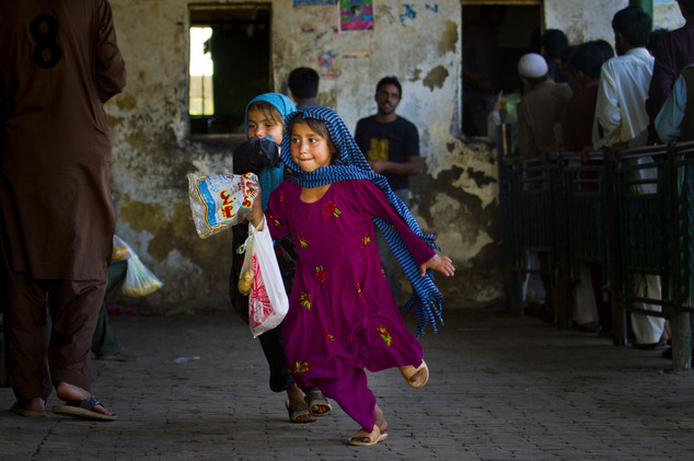 FILE - Girls run toward their friends after getting free food from a distribution point at a shrine in Islamabad, Pakistan, Wednesday, May 18, 2016. (AP Phot...