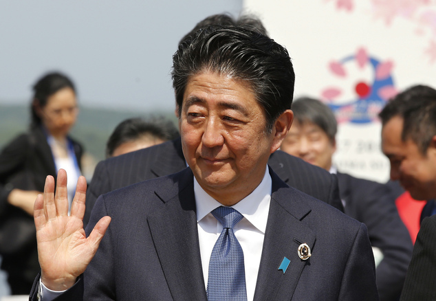 Japanese Prime Minister Shinzo Abe waves to the media after a press conference of the Group of Seven Summit in Shima, central Japan, Friday, May 27, 2016. Th...