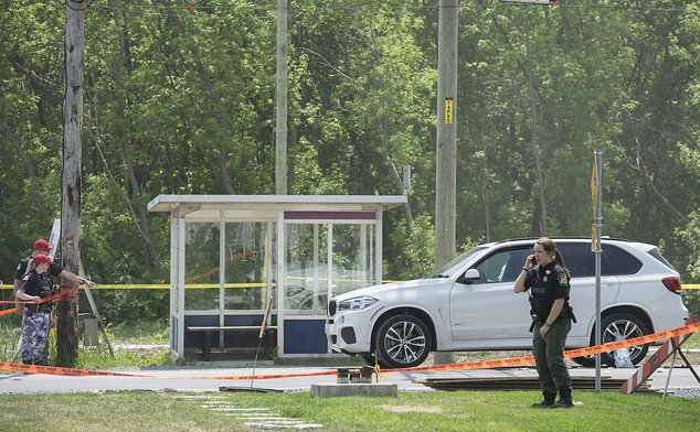 Police officers examine the scene as a white luxury SUV with a broken passenger-side window is shown in Laval, Quebec, Friday, May 27, 2016, where alleged mo...
