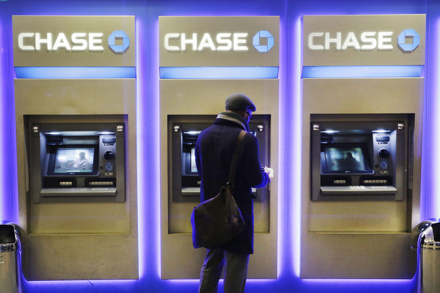 FILE - In this Wednesday, Jan. 14, 2015, file photo, a customer uses an ATM at a branch of Chase Bank, in New York.  JPMorgan Chase, Wells Fargo and other bi...