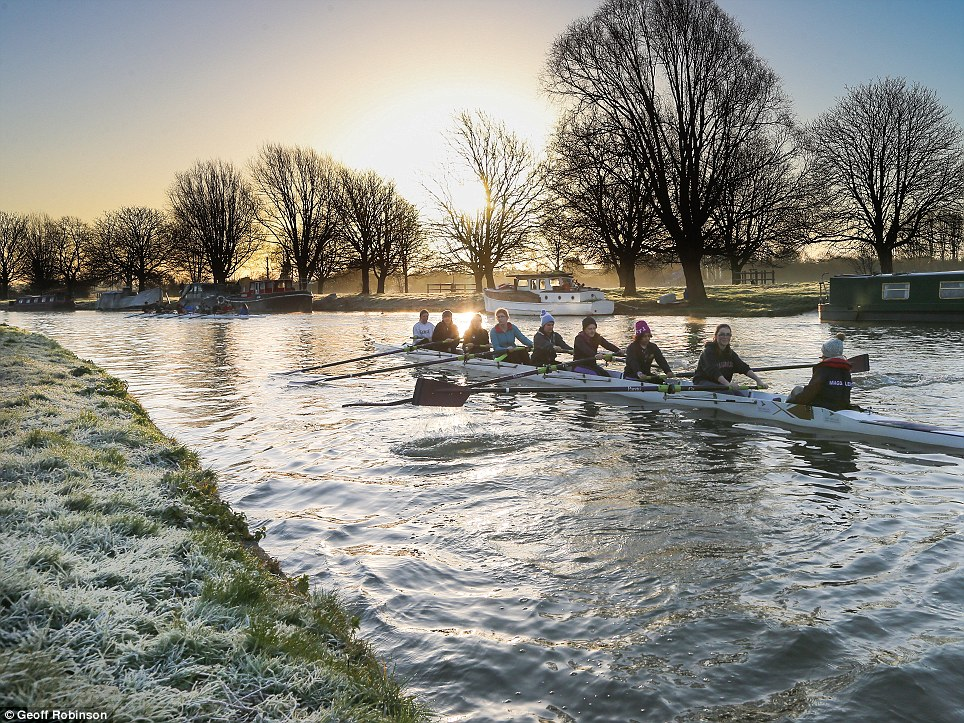 A Cambridge rowing crew passes moored boats on the River Cam as the sun shines through the branches of a leafless tree
