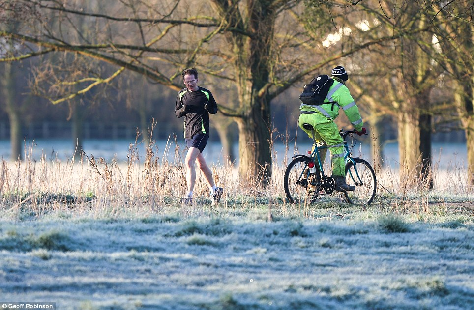 Brave: A jogger and a cyclist on the banks of the River Cam cross paths as they venture out into the early-morning cold. As the temperatures rise over the next few days, frosty conditions could be few and far between over the coming weeks
