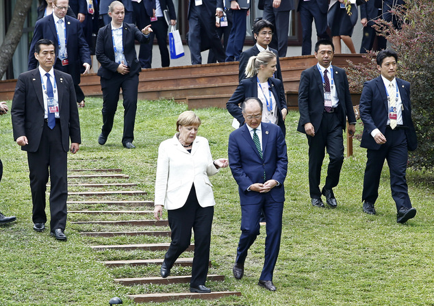 German Chancellor Angela Merkel, left, walks with World Bank President Jim Yong Kim right, during the family photo session at the G7 Ise-Shima Summit in Shim...