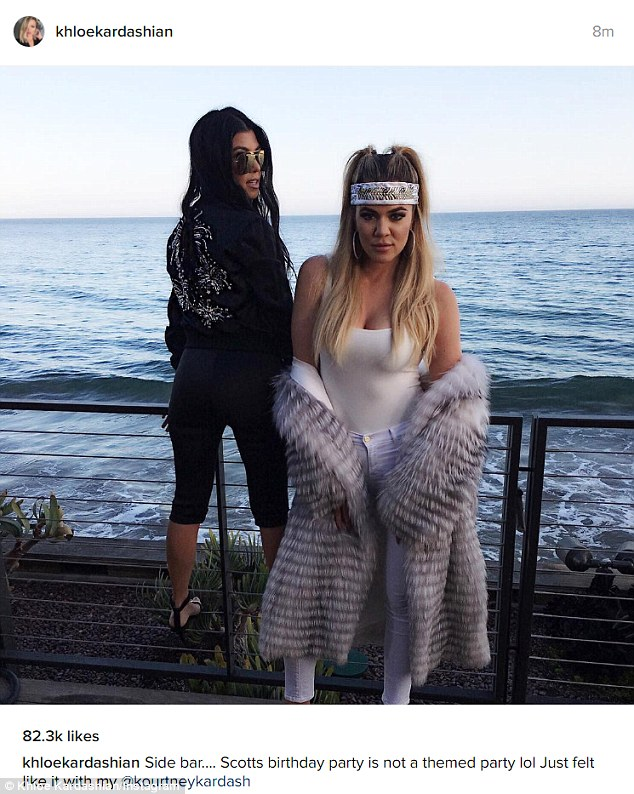 Sisters: Khloe posed provocatively beside her darkly clad sister Kourtney at the seaside restaurant