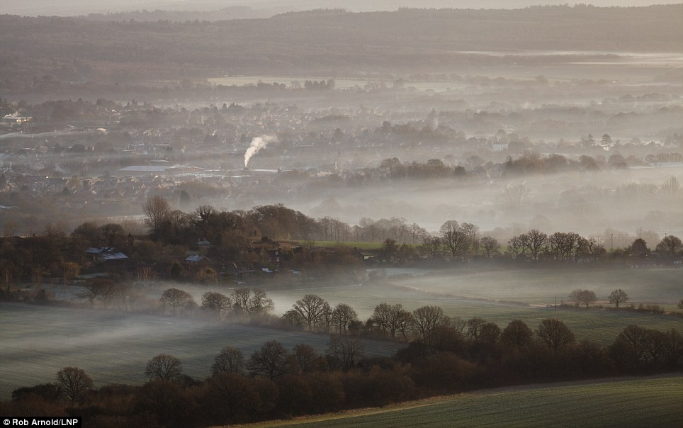 The chimneys of houses in Petersfield, Hampshire, are only barely visible in the early morning weather
