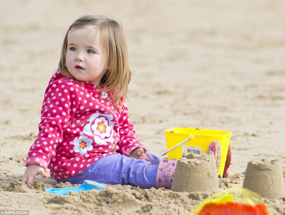 Sandcastle: Two-year-old Faith Bristow makes full use of her bucket and spade for the first time this year on Bournemouth beach