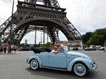 """A person drives a convertible Volkswagen Beetle car in front of the Eiffel tower in Paris, on July 28, 2013, during a vintage cars parade as part of the sixth summer edition of the """"Traversee de Paris Estivale"""" (""""Summer Paris Crossing""""), the largest gathering of classic vehicles in the French capital streets. AFP PHOTO / MIGUEL MEDINA        (Photo credit should read MIGUEL MEDINA/AFP/Getty Images)"""