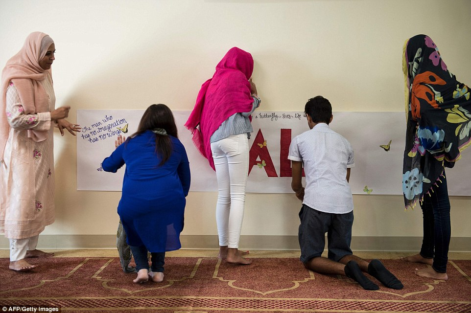 People are seen decorating a banner set up at the interfaith service in tribute to Muhammad Ali with some of his famous quotes, including 'float like a butterfly, sting like a bee'