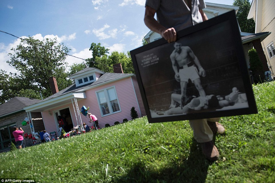 A man carries a photo of Ali outside the boxing legend's childhood home onGrand Avenue, which was recently turned into a museum