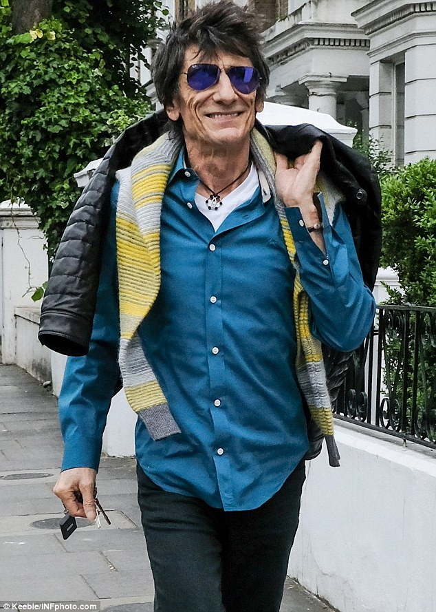 Delighted: The Rolling Stones rocker seemed to be on his way to greet his wife at the hospital