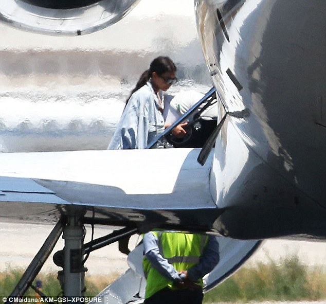 Easy does it: Kim tread the steps leading up into the private jet carefully in those spike-heeled boots