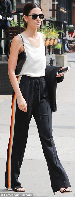 Dressy: She paired her simple blouse with dark trousers that featured a multi-coloured strip down each leg