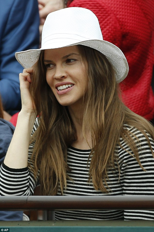 Understated: The actress looked stunning for her stint at the tennis, sitting behind the women's trophies in a simple striped top and chic white hat