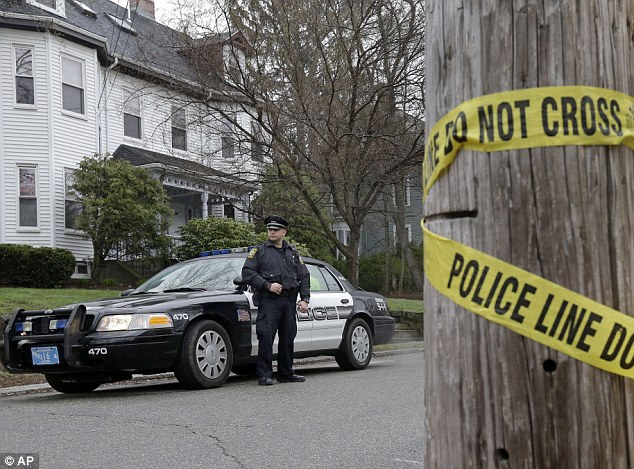 Presence: Police keep watch near the scene where Dzhokhar Tsarnaev was captured last Friday