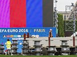Construction workers look at the the Euro 2016 Paris Fan Zone, under construction on the Champs de Mars in Paris, Friday, June 3, 2016. France's interior minister says the Paris police chief wants more security staff to protect fans at the 2016 European Championship, which starts next week. (AP Photo/Kamil Zihnioglu)