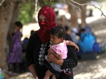 A displaced Iraqi woman who fled the al-Falahat village west of Fallujah holds a child as they wait to receive food and aid at the village of al-Azraqiyah, on June 4, 2016 ©Ahmad Al-Rubaye (AFP/File)