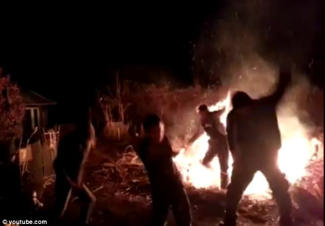 Falling: He then seems to loose his footing on the edge of the bonfire and then falls straight back into the flames