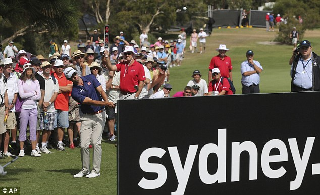 Innovative: Scott chips over a sign on the first hole on his way to a 10-under-par round of 60