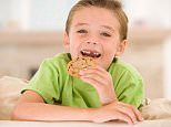 B3K5X2 Young boy eating cookie in living room smiling