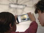 """This image provided by Google shows people looking at a view of the solar system using technology Google calls """"Project Tango."""" Tango uses software and sensors to track motions and size up the contours of rooms, which can empower a smartphone to map building interiors. That¿s a crucial building block of a promising new frontier in ¿augmented reality,¿ or the digital projection of lifelike images and data into a real-life environment. (Courtesy of Google via AP) MANDATORY CREDIT"""