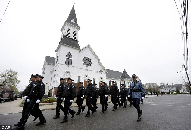 Honor guard: Massachusetts Institute of Technology police officers march as they depart St Patrick's Church in Stoneham, Mass., following a funeral Mass for MIT police officer Sean Collie