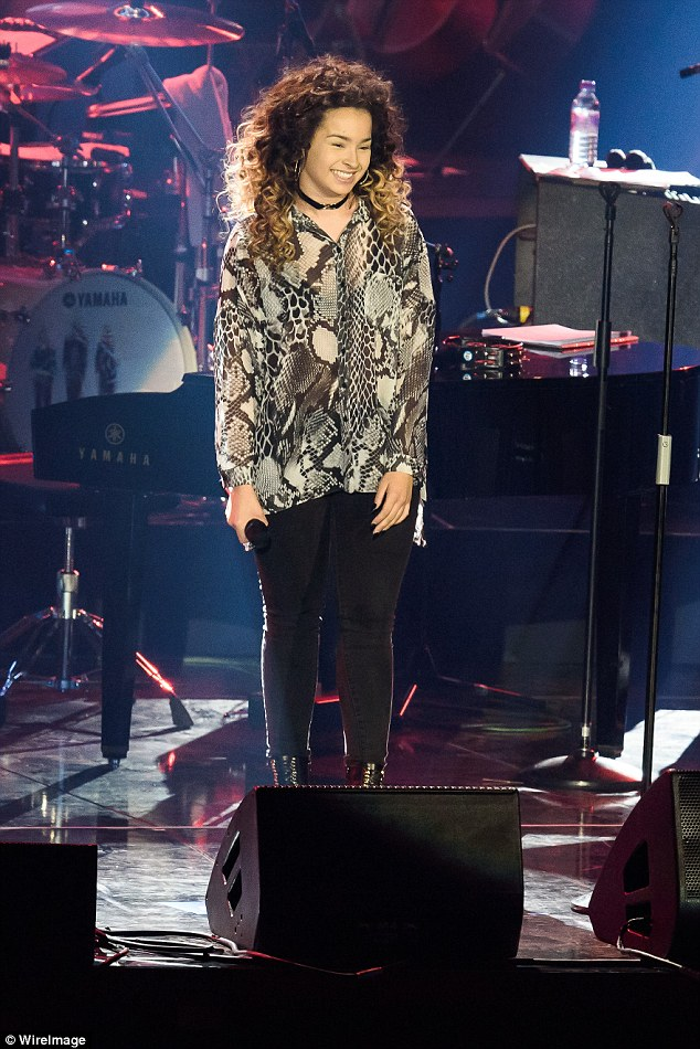 Taking the stage: Ella looked pretty in a snakeskin shirt and skinny black jeans for her performance