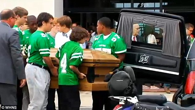 Laid to rest: Members of Daniel's JV football team carried his casket to the hearse at his funeral this past Monday
