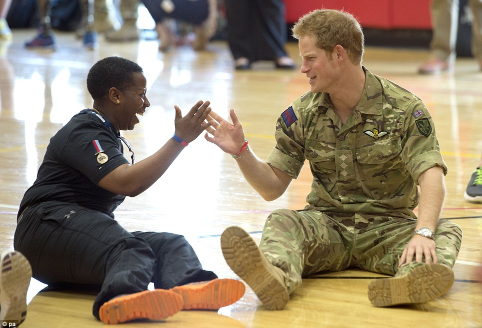 Prince Harry gives a high five to Lcpl Maurillia Simpson: Simpson was blown up by two incoming mortar attacks and then suffered a road traffic accident while serving in Germany