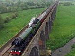 PIC BY NEIL FEDOROWYCZ/CATERS NEWS - (PICTURED: Drone footage of a train journey on the longest masonary viaduct in Britain in Northamptonshire.) - Great Scott! This incredible drone footage of the Flying Scotsman steaming across a picturesque viaduct will take your breath away. The cloudy, grey day was brightened up by the iconic locomotive chugging along the tracks of the Harringworth viaduct in Northamptonshire  the longest masonry viaduct in Britain. Hundreds of amazed onlookers gathered in the field below as the magnificent train sped down the railway on its journey from London to York. After steaming through Wellingborough station, the train stopped at Kettering to pick up passengers and fill up with water before thundering on over the viaduct. The amazing journey was caught on camera by hobby drone operator Neil Fedorowycz, who watched the live action footage streaming through his iPad as he controlled the drone with his wife Marnie. SEE CATERS COPY.