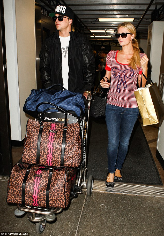 A lot of baggage: River pushed the baggage cart while Paris held onto her gold shopping bag