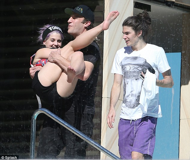 So happy: Kelly giggled with glee as a male friend scooped her up in his arms while fiance Matthew Mosshart smilingly looked on