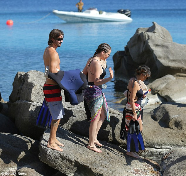 Shortest to tallest: The step-siblings climbed some jagged rocks in height order before pushing off into the surf