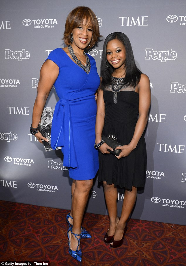 Pint-sized superstar: Gayle posed with Olympic gymnast Gabby Douglas, who looked gorgeous in black dress and maroon peep-toe heels
