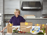 In this photo provided by Marley Spoon, Inc., Martha Stewart poses with ingredients from a meal kit. Cooking like Stewart is about to get easier, as the home goods mogul and cookbook author is getting into the fast-growing meal kit business. Subscribers of the meal kits will be shipped a box to their doors with Stewart¿s recipes and all the ingredients needed to cook up the dishes at home, including pre-measured raw meat, fish, vegetables and spices. The new venture is a licensing deal with existing meal kit company Marley Spoon and brand management company Sequential Brands Group Inc., which bought Martha Stewart Living Omnimedia in 2015. (Marcus Nilsson/Courtesy of Marley Spoon, Inc. via AP) MANDATORY CREDIT