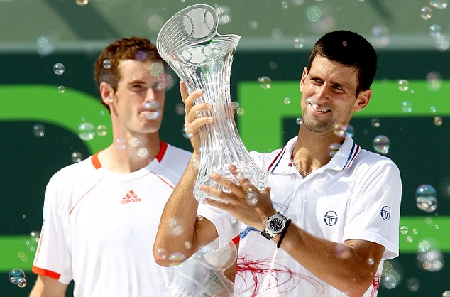 Want: Murray watches as Djokovic raises the trophy