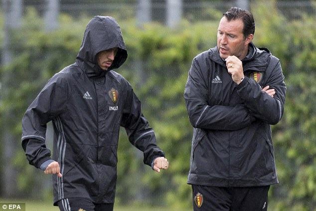 Wilmots chats with Hazard during the session as the winger looks to protect himself from the rain